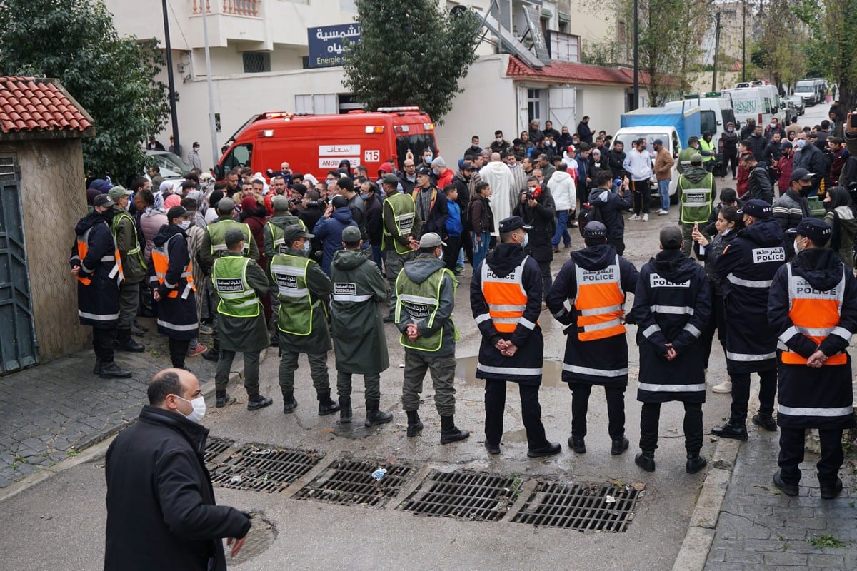 Emergency services gather at the site of illegal underground textile workshop that flooded after heavy rain fall in Morocco's city of Tangiers on 8 February 2021 [AFP/Getty Images]