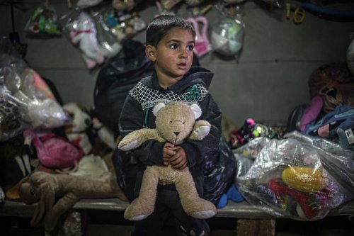 A Syrian child holds a teddy bear at Muhammed Kiteys' toy store for children, at a tent camp in Idlib, Syria on 1 February 2021. [Muhammed Said - Anadolu Agency]