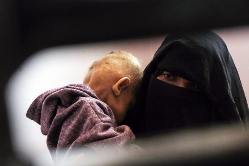 A woman holding her child at a hospital in Sanaa, Yemen on 13 February 2021 [Mohammed Hamoud/Anadolu Agency]