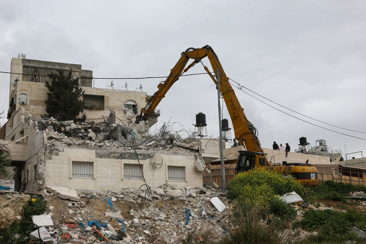 Israeli-run Jerusalem Municipality team along with Israeli soldiers and bulldozers demolish the house owned by a disabled Palestinian Hatim Abu Rayala (R), near the al-Issawiya neighborhood claiming that it was unlicensed, in East Jerusalem on 1 March 2021. [Mostafa Alkharouf - Anadolu Agency]