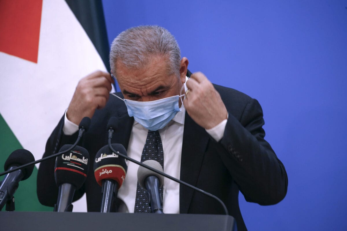 Palestinian Prime Minister Mohammad Shtayyeh puts on a protective mask after holding a press conference in Ramallah on May 5, 2020 [ABBAS MOMANI/AFP via Getty Images]