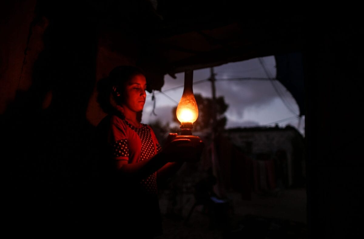 A Palestinian girl uses a gas lamp during a power cut in Gaza on August 18, 2020 [MAHMUD HAMS/AFP via Getty Images]