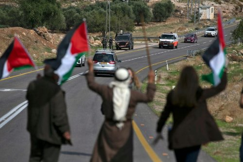 Palestinians block a road to stop Israeli settlers from passing during a demonstration against Jewish settlements in the village Kafr Malik in the Israeli-occupied West Bank, on November 20, 2020 [ABBAS MOMANI/AFP via Getty Images]