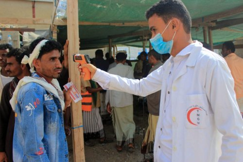 A healthcare worker checks the temperature of displaced Yemenis amid the COVID-19 pandemic on January 12, 2021 [ESSA AHMED/AFP via Getty Images]