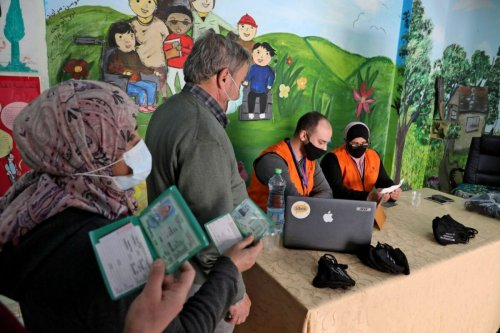 Members of the Palestinian Central Elections Commission register voters in the West Bank town of Hebron on February 10, 2021 [HAZEM BADER/AFP via Getty Images]