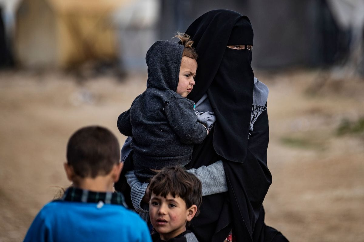 Women and children are pictured at the Kurdish-run al-Hol camp which holds suspected relatives of Islamic State (IS) group fighters, in the northeastern Syrian Hasakeh governorate, on 17 February 2021. [DELIL SOULEIMAN/AFP via Getty Images]