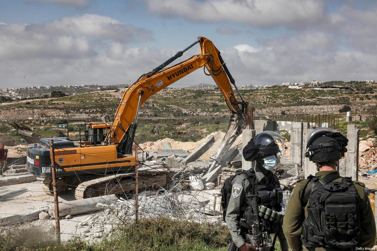 An Israeli soldier and border guard stand by as an excavator demolishes a Palestinian house (still under construction) located within the area C in the occupied West Bank on March 8, 2021 [HAZEM BADER/AFP via Getty Images]