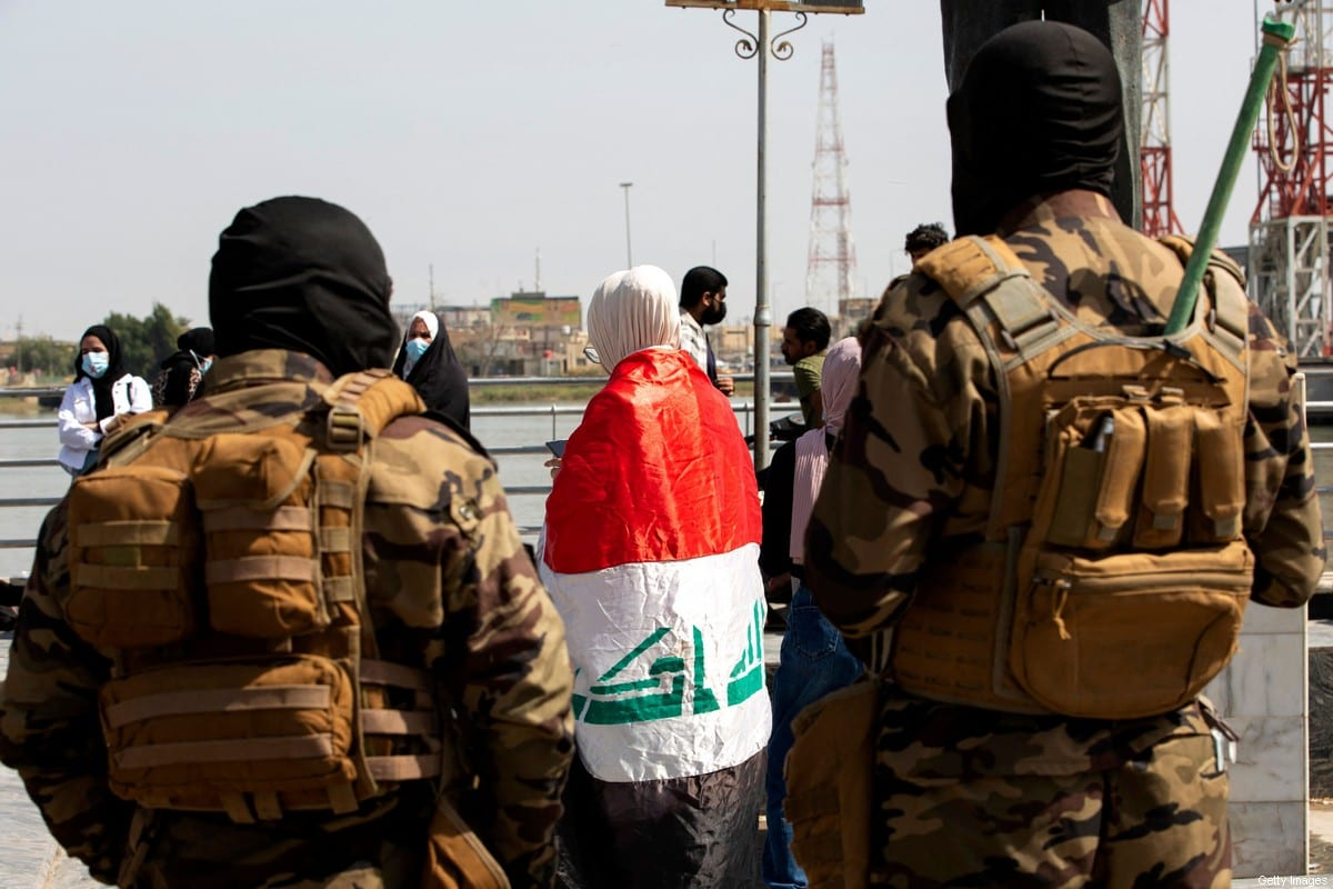 Members of Iraqi security forces look on as a demonstrator stands draped in a national flag durign a rally in Iraq on 8 March 2021 [HUSSEIN FALEH/AFP/Getty Images]