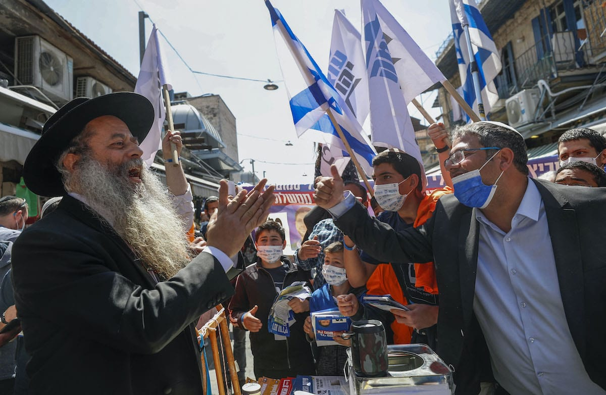Head of Israel's Jewish Power (Otzma Yehudit) party Itamar Ben Gvir (R) talks to supporters through Mahane Yehuda market in Jerusalem, on 19 March 2021. [EMMANUEL DUNAND/AFP via Getty Images]