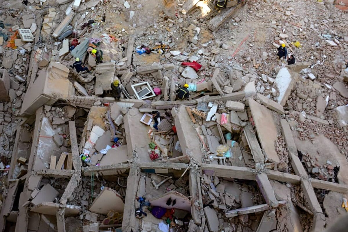 People and rescuers gather around the rubble of a building that collapsed in the popular area of Gesr Suez, east of the Egyptian capital Cairo, on March 27, 2021 [AFP via Getty Images]
