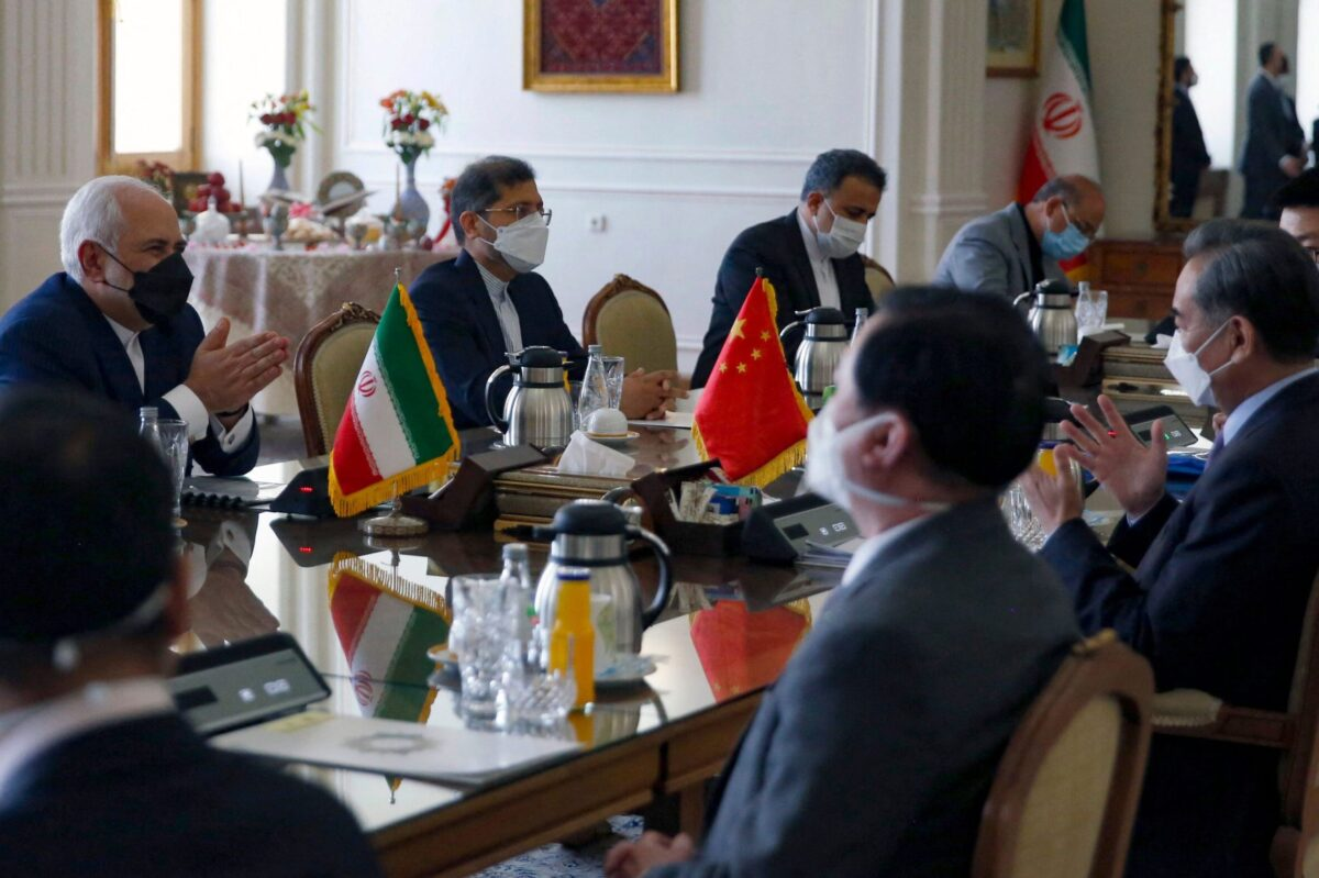 "Iranian Foreign Minister Mohammad Javad Zarif (L) meets with his Chinese counterpart Wang Yi (2-R), in the capital Tehran, on March 27, 2021. - Iran and China signed what state television called a ""25-year strategic cooperation pact"" on today as the US rivals move closer together. The agreement, which has been kept almost entirely under wraps, was signed by the two countries' foreign ministers, Mohammad Javad Zarif and Wang Yi, an AFP correspondent reported. (Photo by - / AFP) (Photo by -/AFP via Getty Images)"