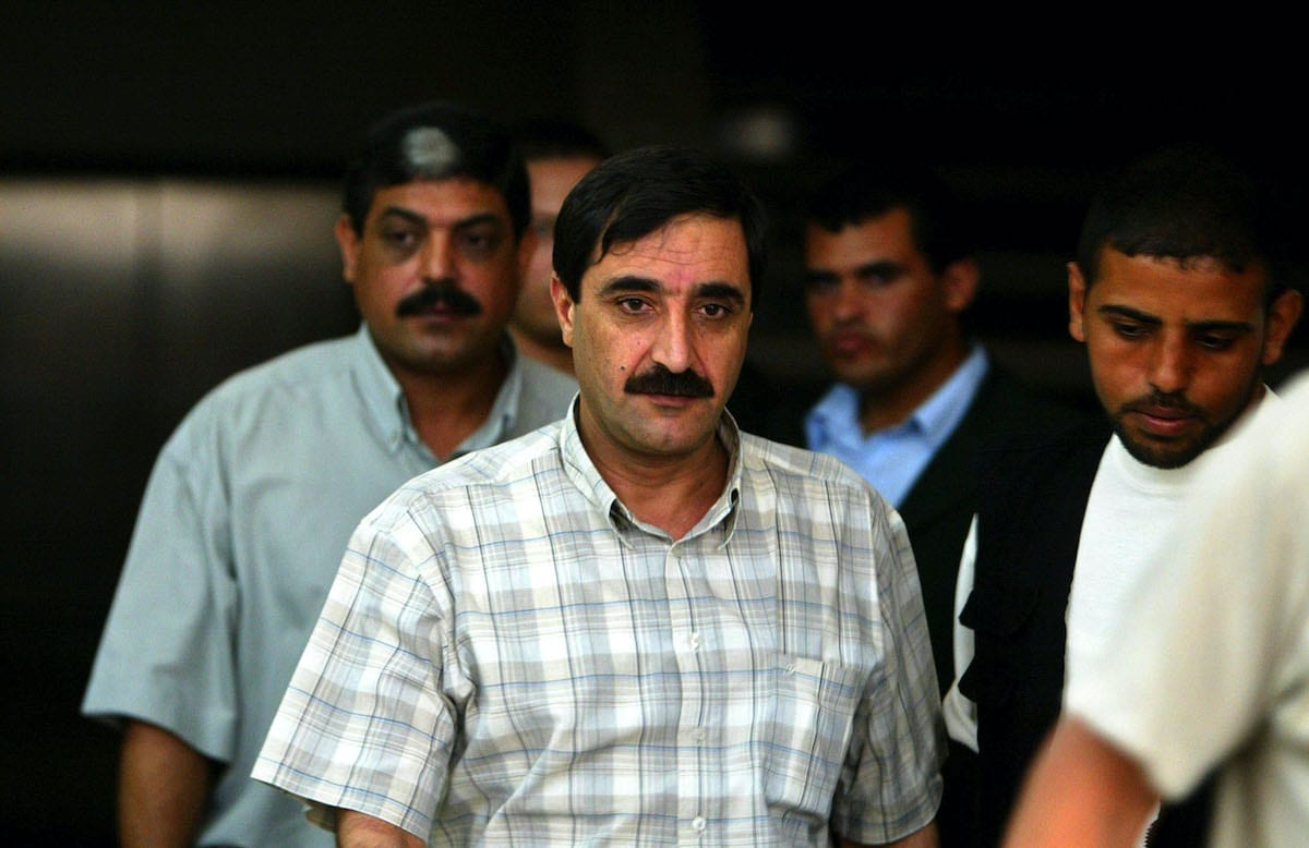 Palestinian Rashed Abu Shbak (C), the head of preventive security in the Gaza Strip, walks out after the meeting of security commanders with Palestinian security chief Mohammed Dahlan on 20 August 2003 at his office in Gaza City, Gaza Strip. [Abid Katib/Getty Images]