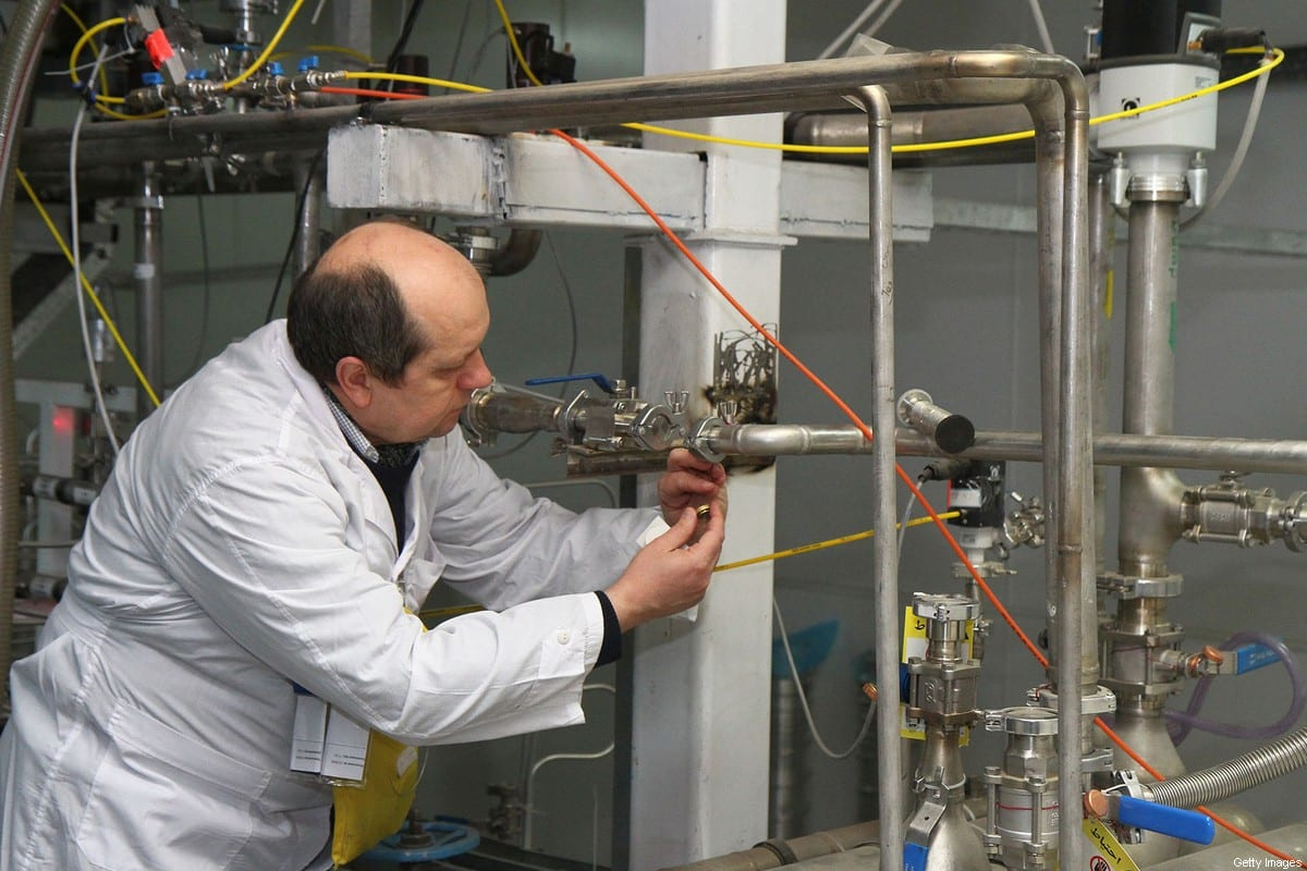 An unidentified International Atomic Energy Agency (IAEA) inspector disconnects the connections between the twin cascades for 20 percent uranium production at nuclear research centre of Natanz, some 300 kilometres south of Tehran on 20 January, 2014 [KAZEM GHANE/IRNA/AFP via Getty Images]