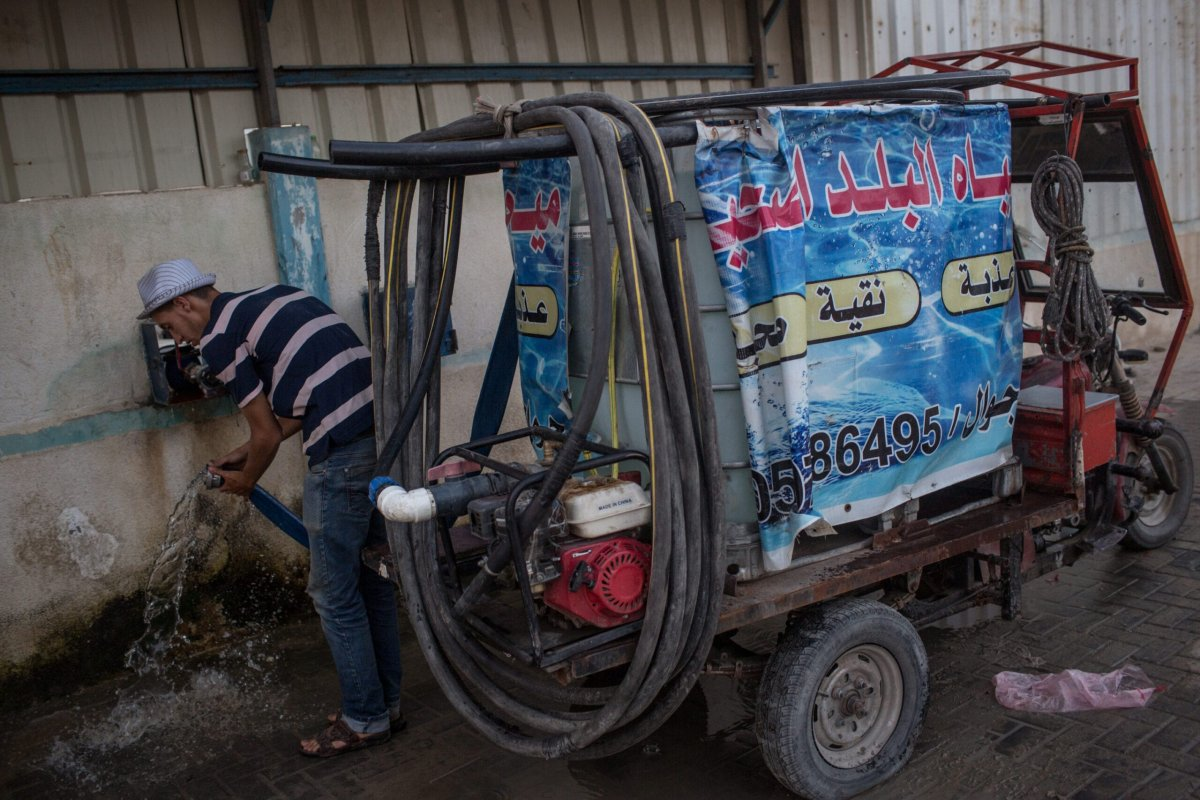 A man disconnects a hose from his water truck after refilling at a water depot on July 20, 2017 in Gaza City, Gaza [Chris McGrath/Getty Images]