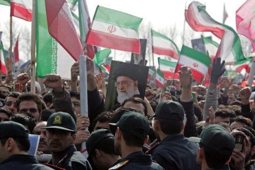 Iranian security froces stand guard as tens of thousands of Iranians, waving national flags and portraits of Supreme leader Ayatollah Ali Khamenei, attend a mass rally held in Tehran on February 11, 2010 [ATTA KENARE/AFP via Getty Images]