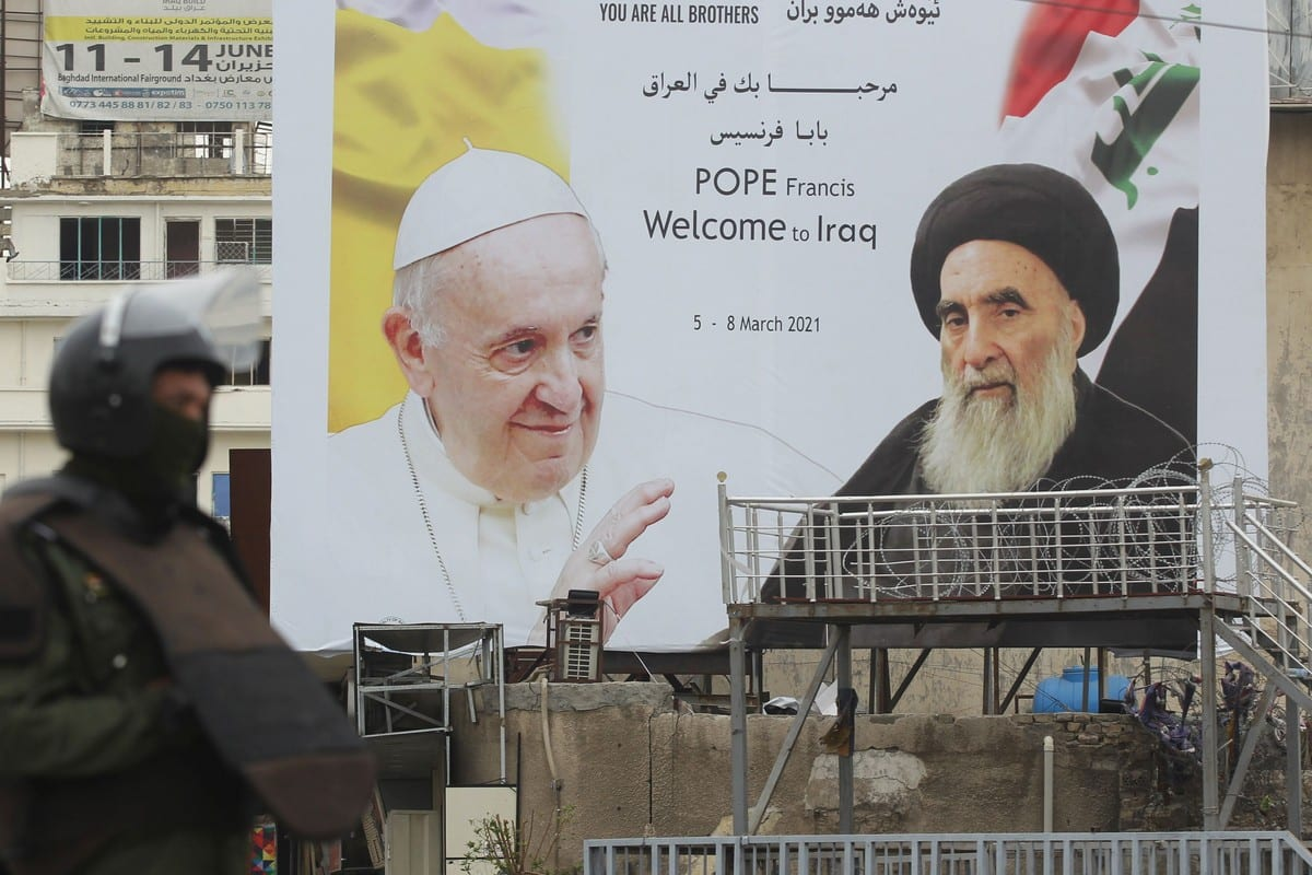 An Iraqi security guard stands in front of a huge billboard bearing portraits of Pope Francis and Grand Ayatollah Ali Sistani (R) in central Baghdad on 4 March 2021 [AHMAD AL-RUBAYE/AFP/Getty Images]