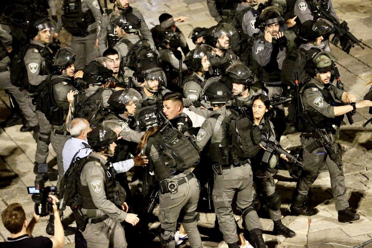 Israeli forces crowd around a Palestinian man in Jerusalem on 18 April 2021 [Mostafa Alkharouf/Anadolu Agency]