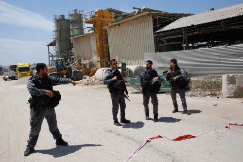 Members of the Israeli security forces gather in front of a damaged factory [GIL COHEN-MAGEN/AFP via Getty Image]
