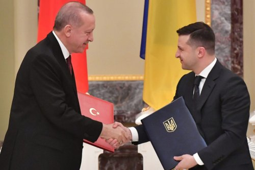 Ukrainian President Volodymyr Zelensky and his Turkish counterpart Recep Tayyip Erdogan exchange documents during a signing ceremony following their meeting in Kiev on February 3, 2020 [SERGEI SUPINSKY/AFP via Getty Images]