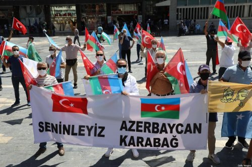 Activists hold flags of Turkey and Azerbaijan as they gather in Ankara, on 8 August 2020 [ADEM ALTAN/AFP/Getty Images]