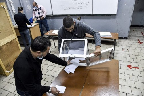 Poll station workers empty a ballot box to begin counting after a vote on a revised constitution ended at a station in Algeria's capital Algiers on November 1, 2020 [RYAD KRAMDI/AFP via Getty Images]