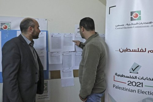 Employees of the Palestinian Central Elections Commission display electoral lists ahead of the upcoming general elections, at the commission's district offices in the city of Hebron in the Israeli-occupied West Bank, on April 6, 2021 [HAZEM BADER/AFP via Getty Images]