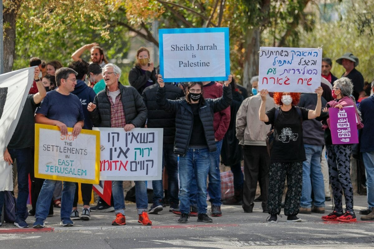 Palestinian, Israeli, and foreign activists lift banners and placards during a demonstration against Israeli occupation and settlement activity in the Palestinian Territories and east Jerusalem, in Jerusalem's Palestinian Sheikh Jarrah neighbourhood, on April 9, 2021 [AHMAD GHARABLI/AFP via Getty Images]