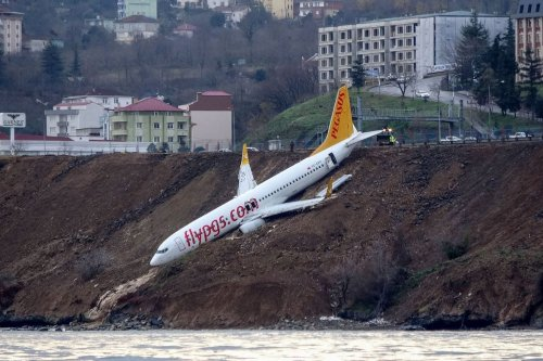 A Pegasus Airlines Boeing 737 passenger plane is seen struck in mud on an embankment, a day after skidding off the airstrip, after landing at Trabzon's airport on the Black Sea coast on 14 January 2018. [AFP via Getty Images]