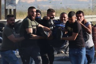 An injured Palestinian is being carried by others at a protest in front of Nablus city's Havara check-point, against Israeli forces' attacks over East Jerusalem and Gaza, on May 14, 2021, in Nablus, West Bank. [Nedal Eshtayah / Anadolu Agency]