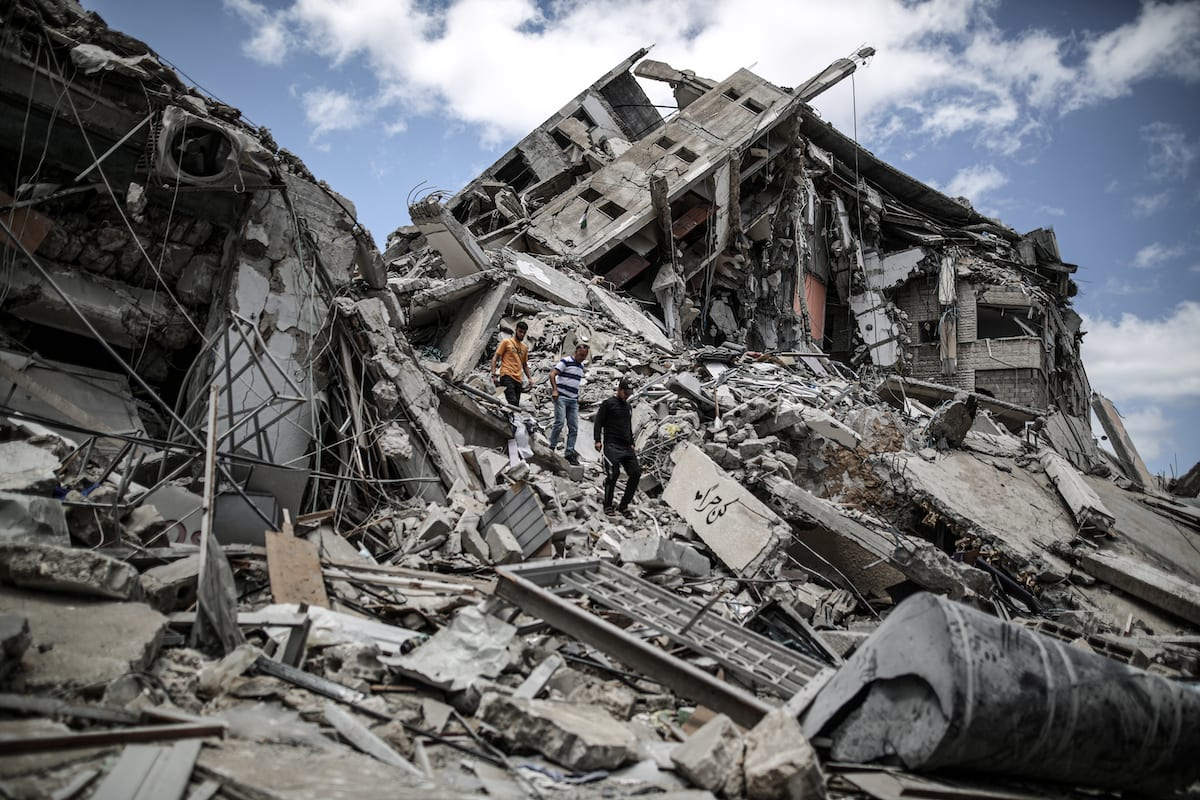 Palestinians clear debris from their shops, which were damaged in Israeli attacks, in Gaza on 22 May 2021 [Ali Jadallah/Anadolu Agency]