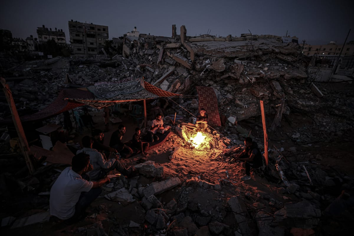 People gather around a fire on the rubbles of a destroyed home in Gaza on 29 May 2021 [Ali Jadallah/Anadolu Agency]