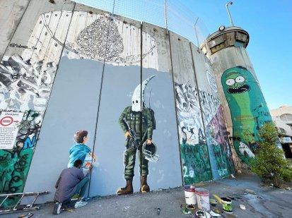 Palestinian artist Taqi Spateen paints the violations of Israeli soldiers against Palestinian children on discrimination wall in Bethlehem, West Bank on May 30, 2021 [Hisham K. K. Abu Shaqra/Anadolu Agency]