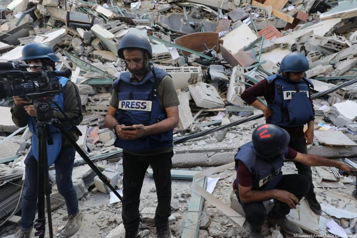 Journalists are seen among the damaged buildings after Israel carried out air strikes in Gaza on 17 May 2021 [Mohammed Asad/Middle East Monitor]