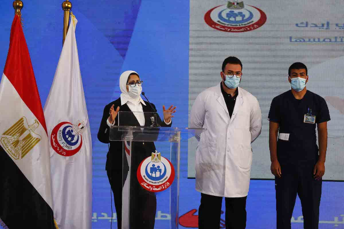 (L to R) Egyptian Health Minister Hala Zayed gives a press conference, accompanied by doctor Abdelmouim Selem and medical staff member Ahmed Hemdan, in a tent set up outside the Abou Khalifa hospital, in Ismailia, about 120kms east the capital Cairo, on 24 January 2021, after the two men received a dose of a coronavirus vaccine. [KHALED DESOUKI/AFP via Getty Images]