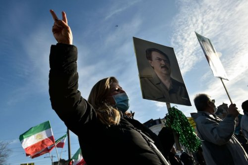 People wave former flags of Iran and hold portraits as they protest outside the Antwerp courthouse, on 4 February 2021, during the trial of four suspects including an Iranian diplomat accused of taking part in a plot to bomb an opposition rally in France. [JOHN THYS/AFP via Getty Images]