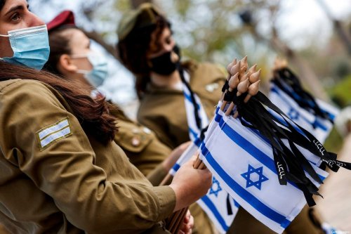 Female soldiers hold Israeli national flags in Tel Aviv on 13 April 2021 [JACK GUEZ/AFP via Getty Images]