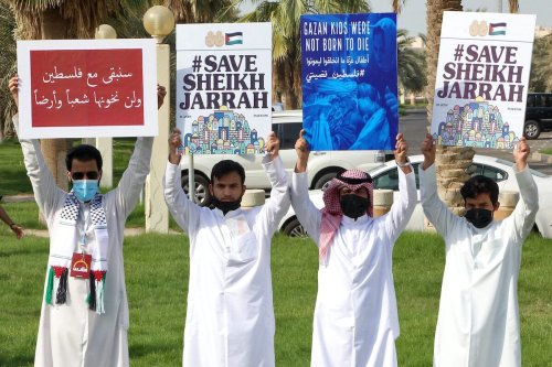 Kuwaitis hold up signs during a protest in solidarity with the Palestinian people in Kuwait City on 11 May 2021. [YASSER AL-ZAYYAT/AFP via Getty Images]