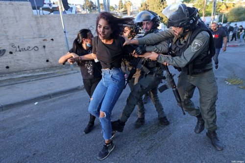 Israeli security forces try to detain a Palestinian woman in the east Jerusalem neighbourhood of Sheikh Jarrah, where looming evictions of Palestinian families have fuelled anger, on May 15, 2021 [EMMANUEL DUNAND/AFP via Getty Images]