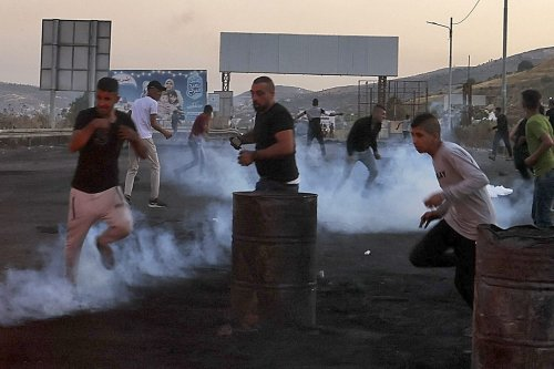 Palestinian protesters rush off to avoid tear gas amid clashes with Israeli security forces at the Hawara checkpoint south of Nablus city, in the occupied West Bank, on May 16, 2021 [AAFAR ASHTIYEH/AFP via Getty Images]