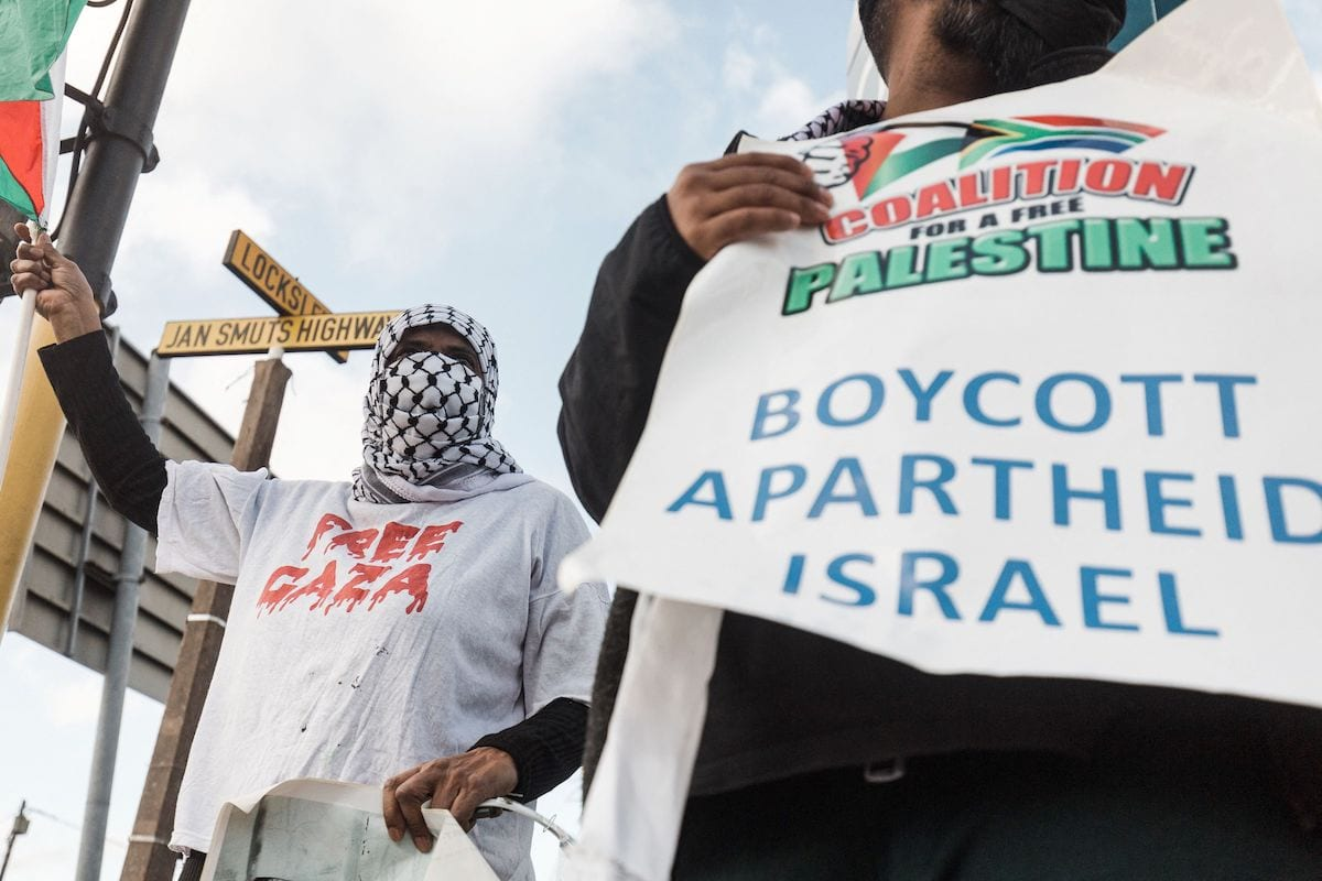 Pro-Palestinian supporters hold placards reading 'Boycott Apartheid Israel' during a protest to condemn the ongoing Israeli air strikes on Gaza, in Durban on 18 May 2021. [RAJESH JANTILAL/AFP via Getty Images]