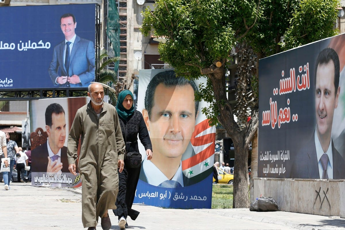 People walk past billboards depicting Syrian President Bashar Al-Assad in Damascus, on 24 May 2021 [LOUAI BESHARA/AFP/Getty Images]