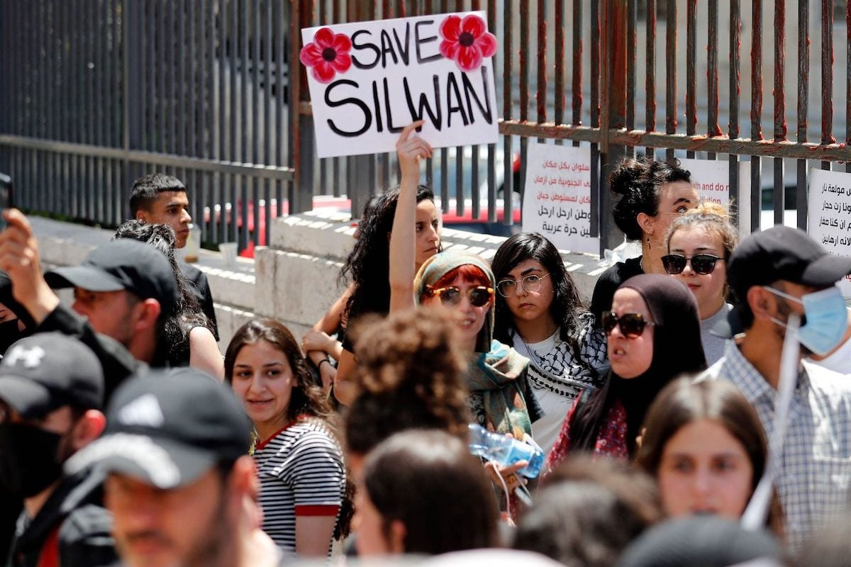 Palestinians shout slogans outside the court in Jerusalem on May 26, 2021 during a protest over Israel's planned evictions of Palestinian families from homes in the eastern sector's Silwan district. [AHMAD GHARABLI/AFP via Getty Images]