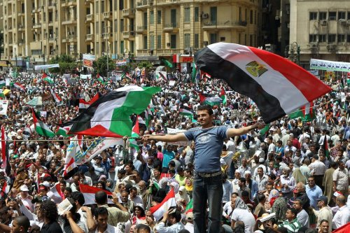 """An Egyptian demonstrator waves Egyptian (R) and Palestinian flags as thousands gather at Cairo's Tahrir Square on 13 May 2011 during a protest calling for national unity after attacks on Egyptian churches, and solidarity with the Palestinians as they mark the """"Nakba"""" or """"catastrophe"""" [KHALED DESOUKI/AFP via Getty Images]"""
