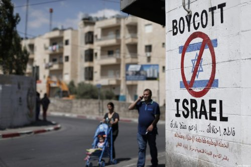 Palestinians walk past a sign painted on a wall in the West Bank calling to boycott Israeli products coming from settlements, 5 June 2019 [THOMAS COEX/AFP/Getty Images]