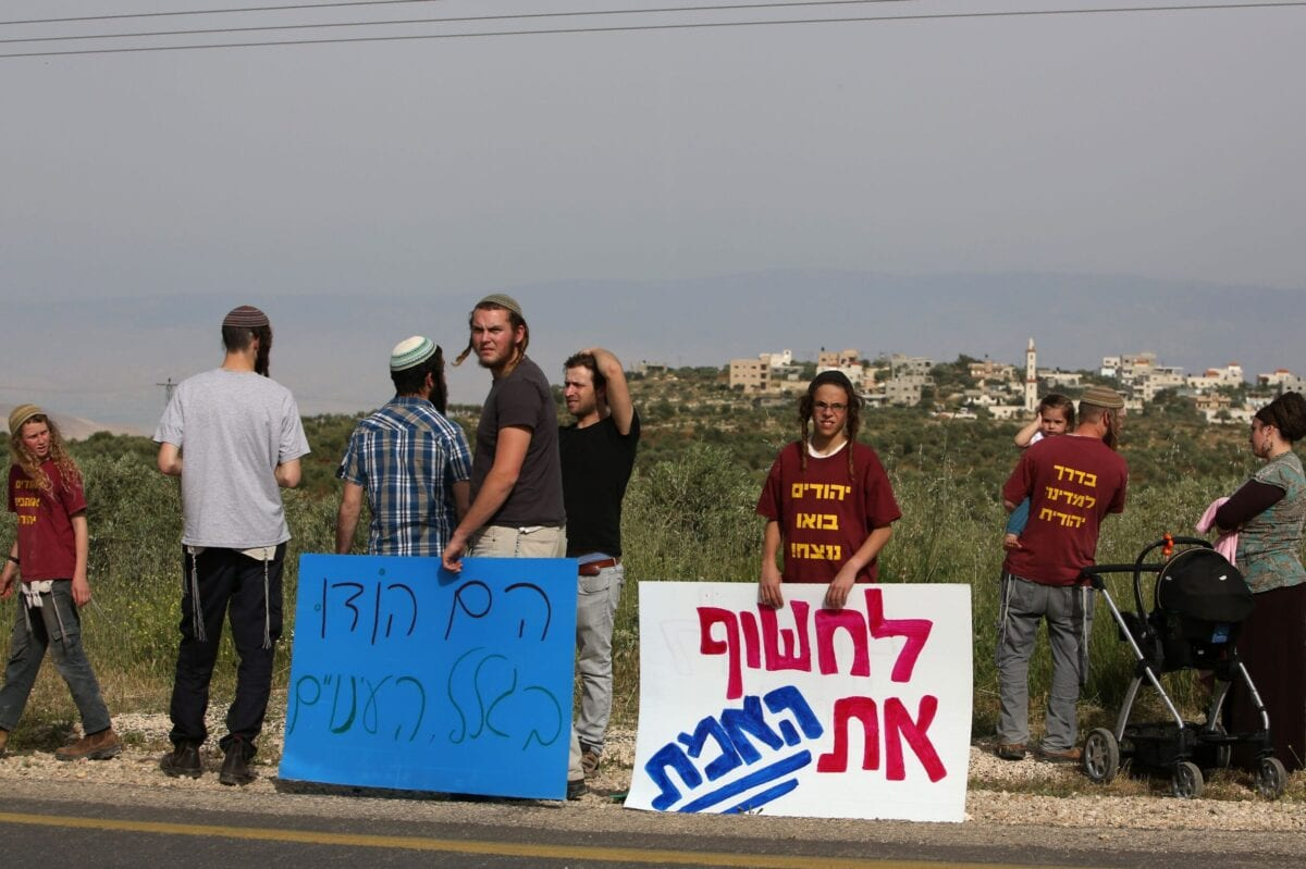 Israeli right-wing activists from nearby settlements protest on the main road leading to the Palestinian village of Duma in the Israeli occupied West Bank on April 5, 2016 [MENAHEM KAHANA/AFP via Getty Images]