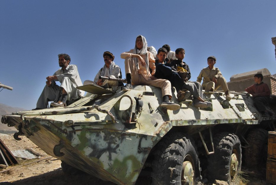 Afghans sit on an abandoned Soviet tank in the Panjshir Valley, 10 September 2006 [SHAH MARAI/AFP via Getty Images]