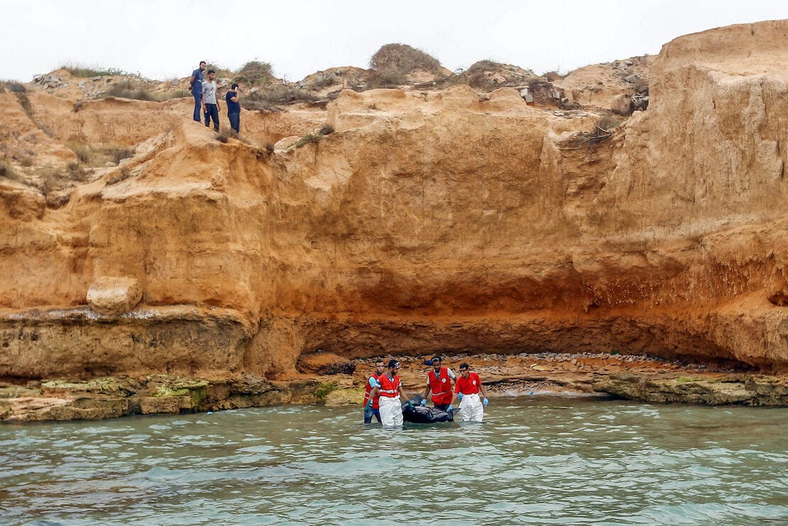 Members of the Libyan Red Crescent recover the body of a drowned migrant off the coast of Tajoura, east of the capital Tripoli, on 3 July 2018. [MAHMUD TURKIA/AFP via Getty Images]