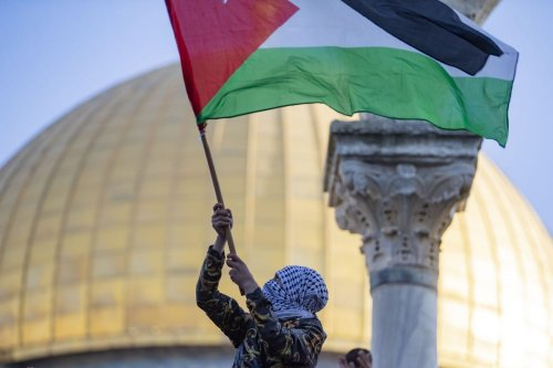 A Palestinian man waves a the Palestinian flag at the Al-Aqsa Compound in Jerusalem on 13 May 2021 [Mostafa Alkharouf/Anadolu Agency]