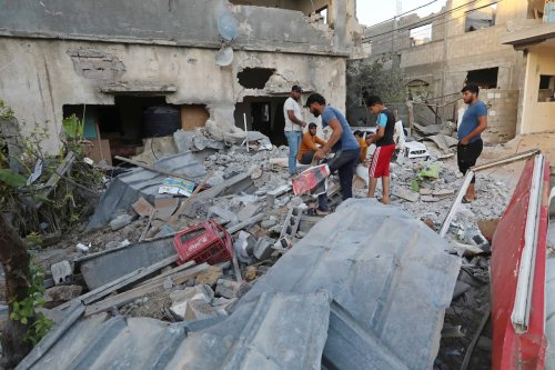 Palestinians are seen amid buildings damaged by the Israeli attacks in in Gaza on 7 June 2021 [Ashraf Amra/Anadolu Agency]