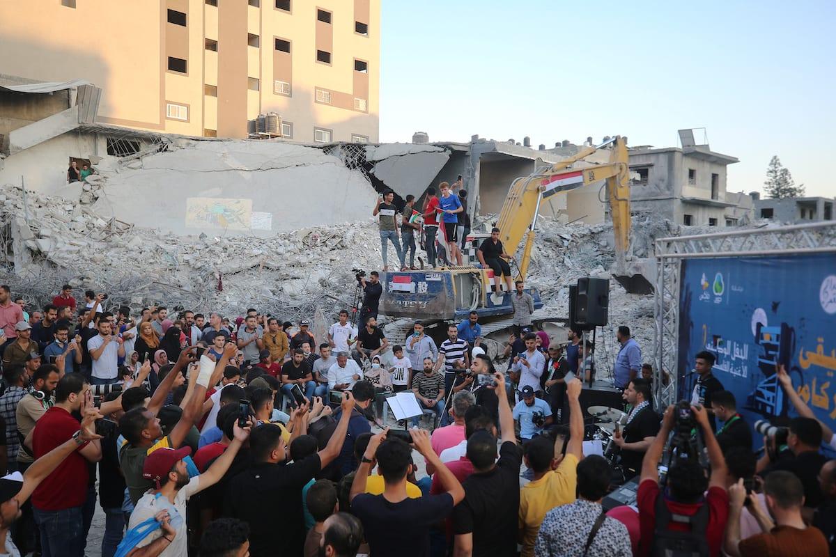 Palestinian Meddah Al-Kamar music band perform on the rubble of the al Shorouq Tower in Gaza City, on June 27, 2021 [Mustafa Hassona / Anadolu Agency]